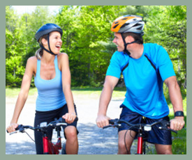 couple with helmets cycling & laughing